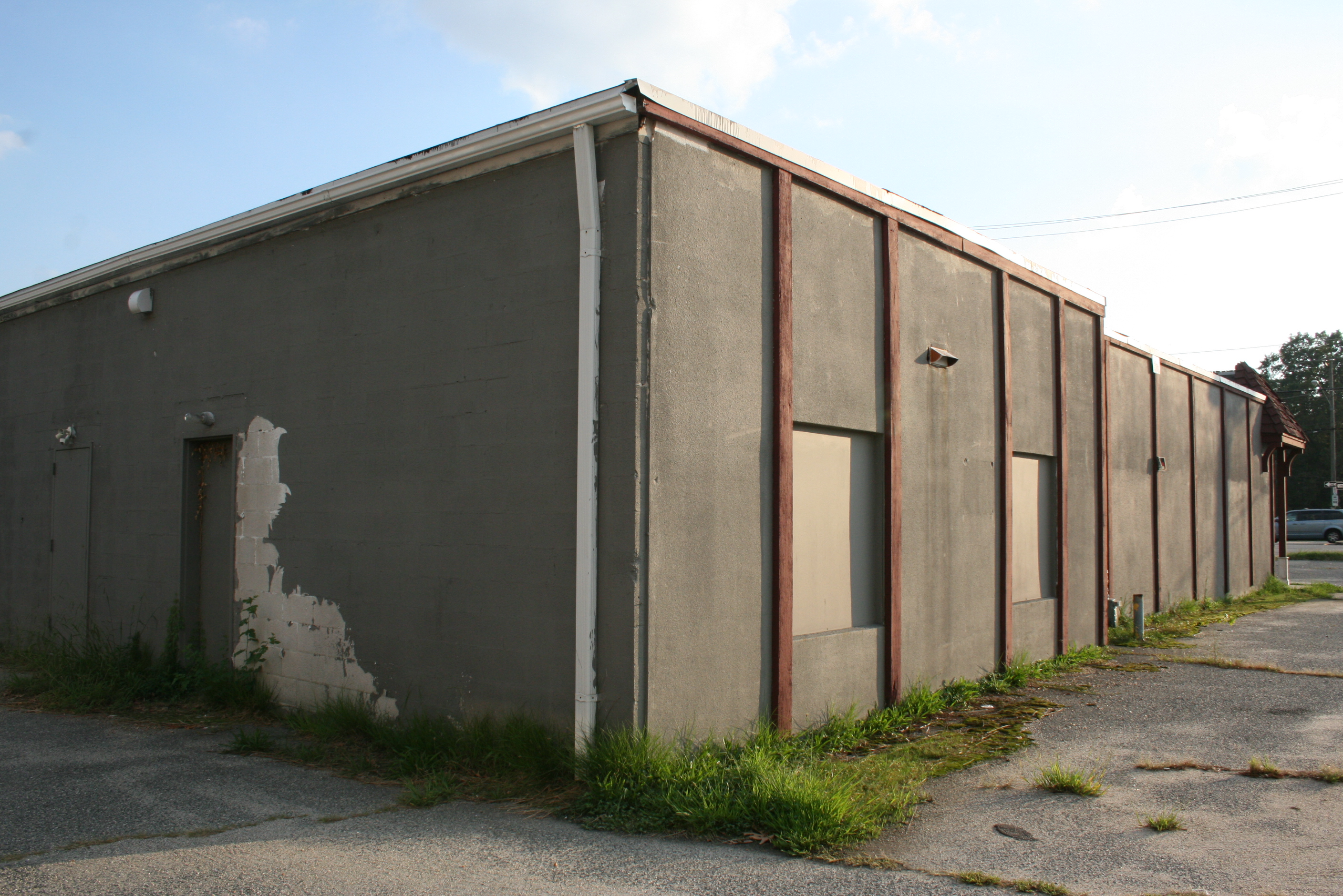 Boarded up windows, overgrown weeds.